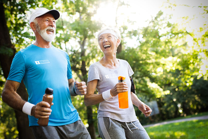 active-mature-couple-running-in-the-park-for-helat-4L6PYLC